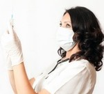 Picture of dark-haired woman wearing white surgical mask, white scrubs, stethoscope, and plastic surgical gloves, with her hands up and looking at the needle she is holding