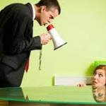 Picture with light green background of man in black suit with red and white bullhorn, standing over and looking down at crouched female co-worker behind glass table, yelling while she looks up at him fearfully, only her head and hands on table visible
